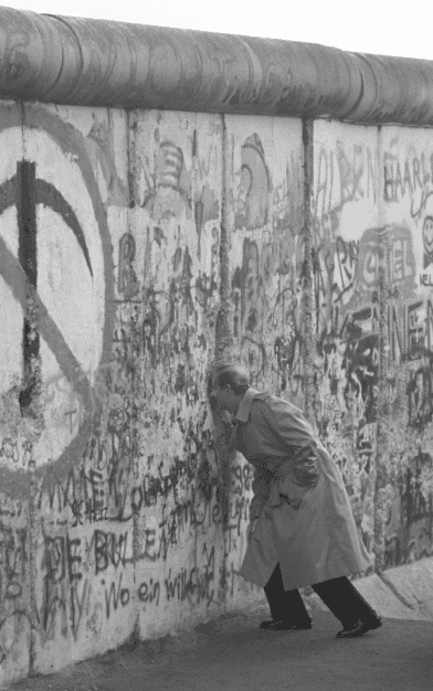 James Baker peers through the Berlin Wall, 12 December 1989